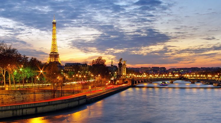 Paris nightlife on the River Seine with Eiffel Tower and Alexandre III Bridge lit.