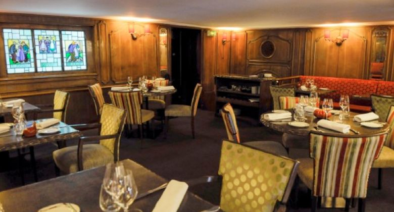Interior of Loiseau Rive Droite, Paris restaurant, featuring stained glass, wood paneling and bayadères seating.